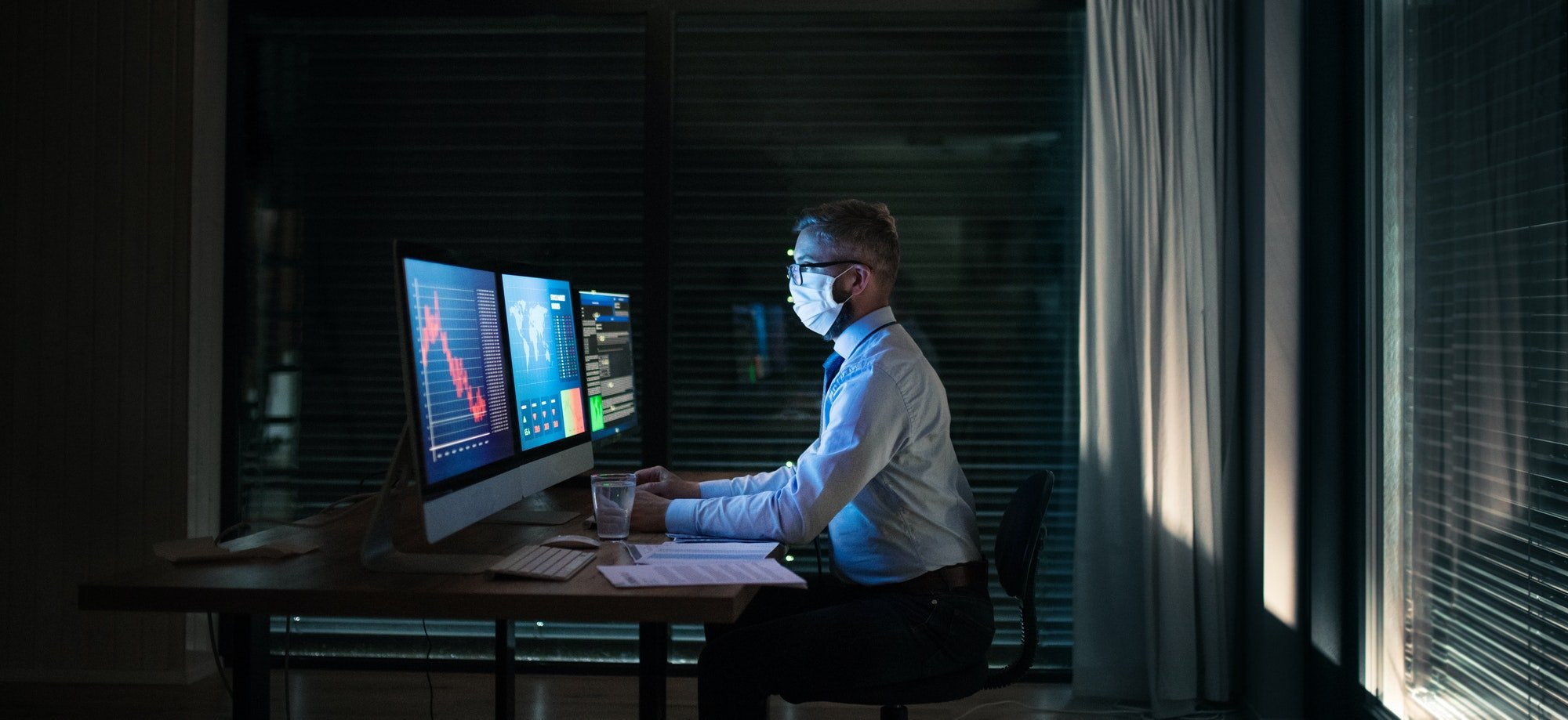Businessman with computer sitting at desk, working late. Financial crisis concept